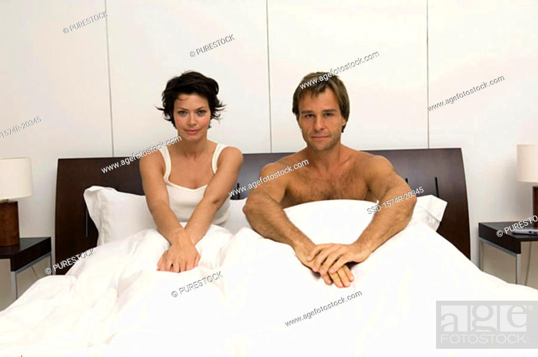 Stock Photo: Portrait of a young couple sitting in the bed.