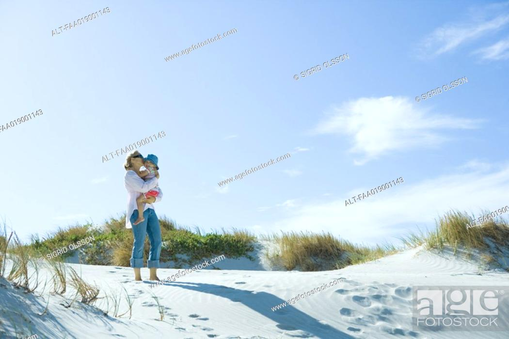 Stock Photo: Mother and daughter standing on dune.
