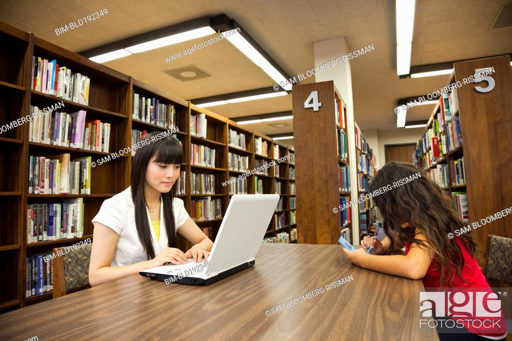Stock Photo: Woman on laptop and girl on video game in library.