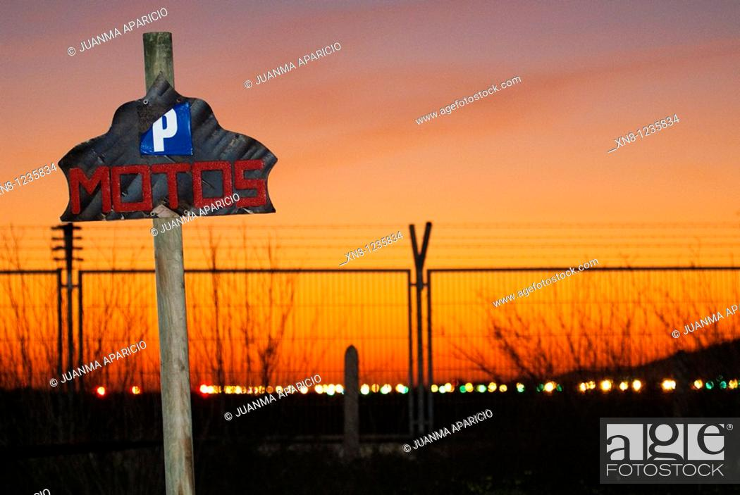 Imagen: Wooden post indicating the aterdecer Motorcycle Parking on a red sky near the airport of Ibiza.