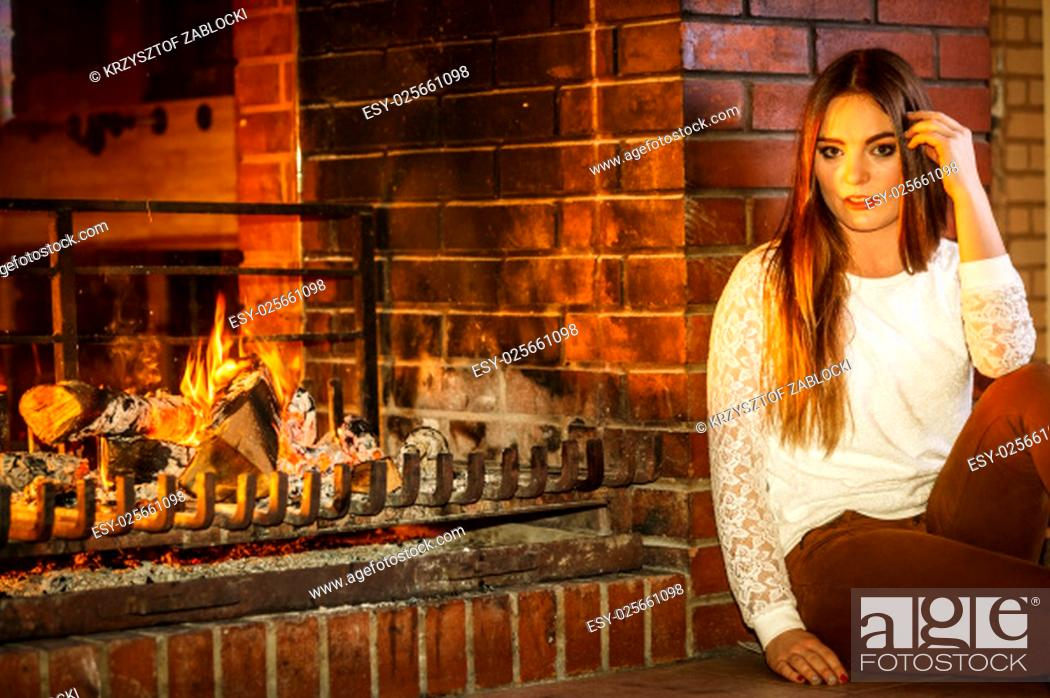 Stock Photo: pensive woman relaxing at fireplace. winter home.