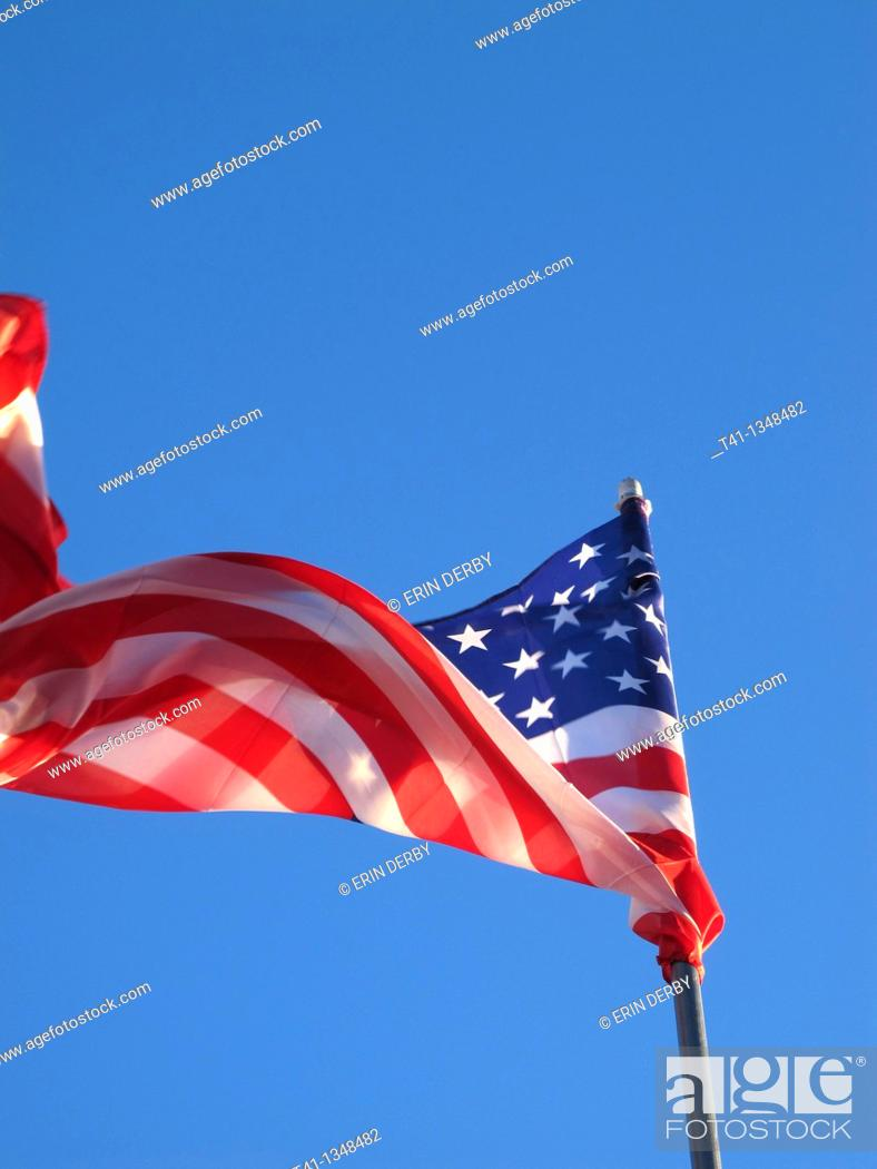 Stock Photo: The American Flag blowing in the wind against a blue sky.