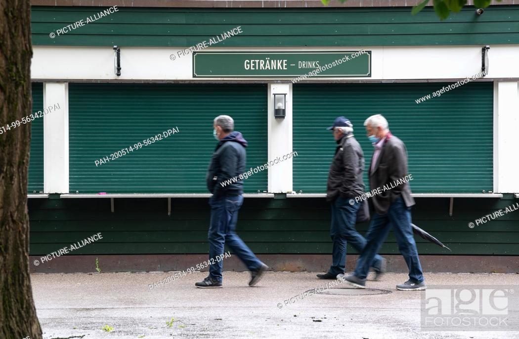 Stock Photo: 14 May 2020, Bavaria, Munich: Three men with masks walk past the drinks counter of the beer garden at the China Tower. From 18 May.