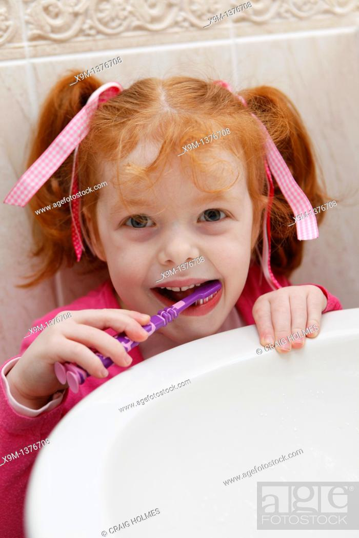 Stock Photo: Little girl at home, brushing teeth in bathroom.