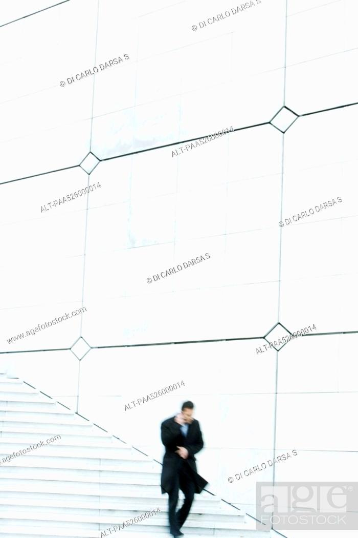 Stock Photo: Businessman descending outdoor stairs, talking on cell phone, holding coat closed against the wind.