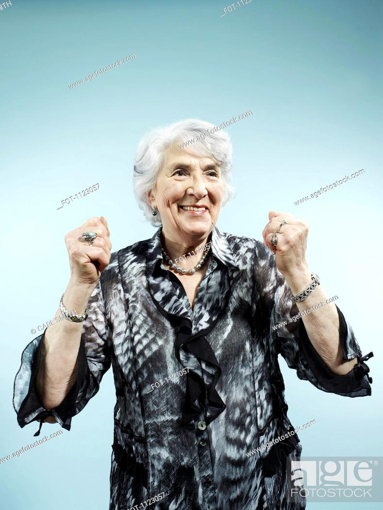 Stock Photo: A senior woman with her arms raised in celebration.