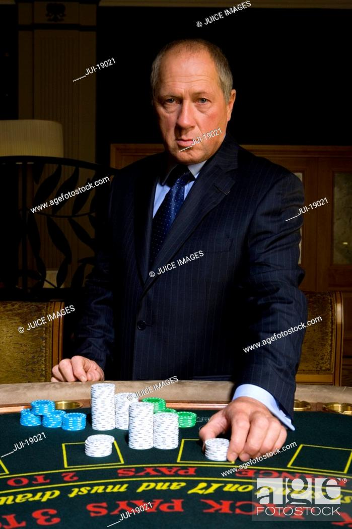 Stock Photo: Mature man placing gambling chips on poker table, portrait.