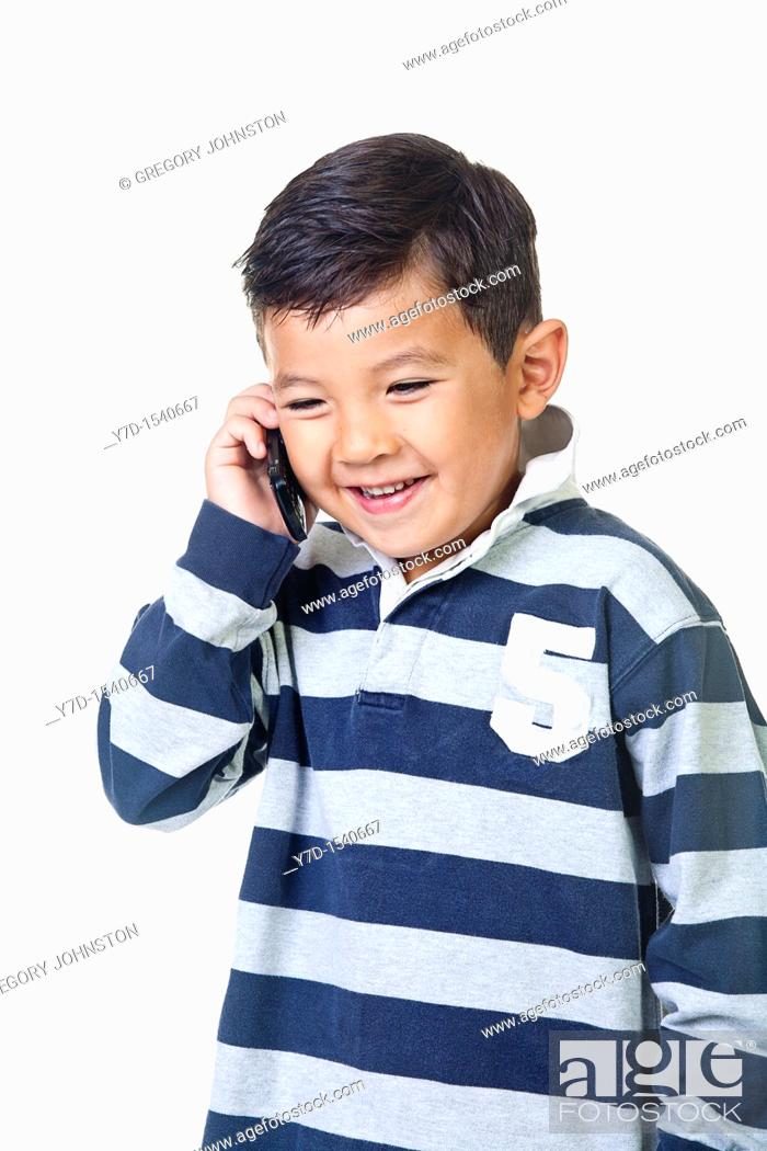 Stock Photo: A young boy talks on the cell phone.