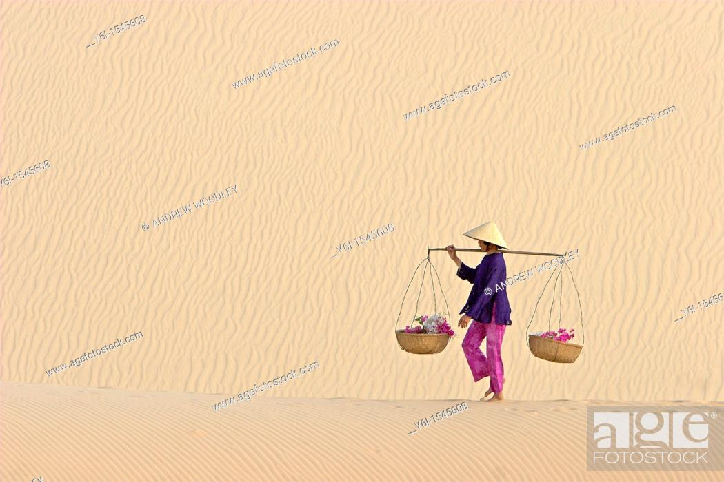 Stock Photo: Woman with conical hat carries flowers in pannier baskets across white sand dunes near Mui Ne Vietnam.