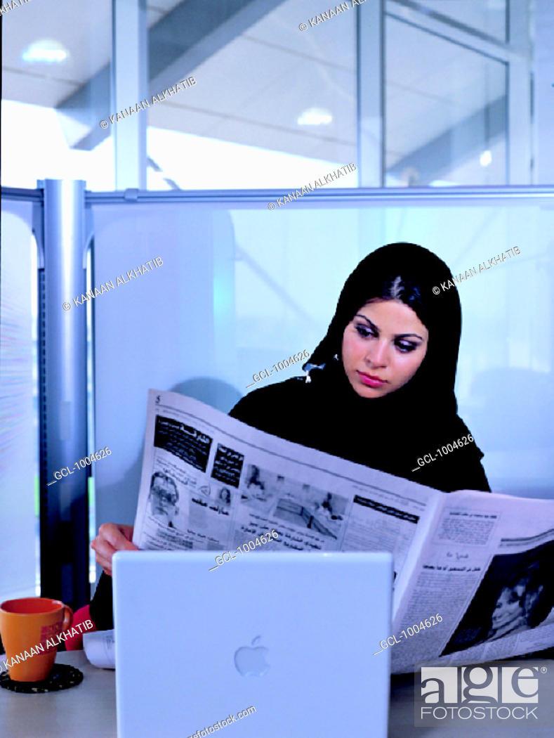 Stock Photo: Emirati businesswoman reading newspaper in the office.