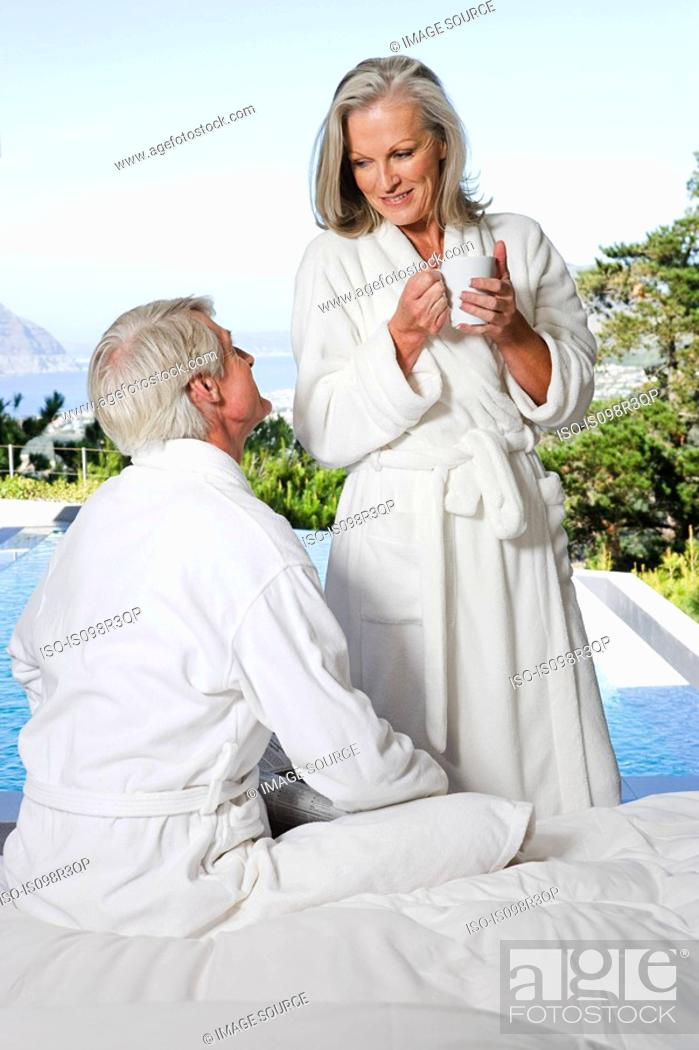 Stock Photo: Middle aged couple in bathrobes by the pool.