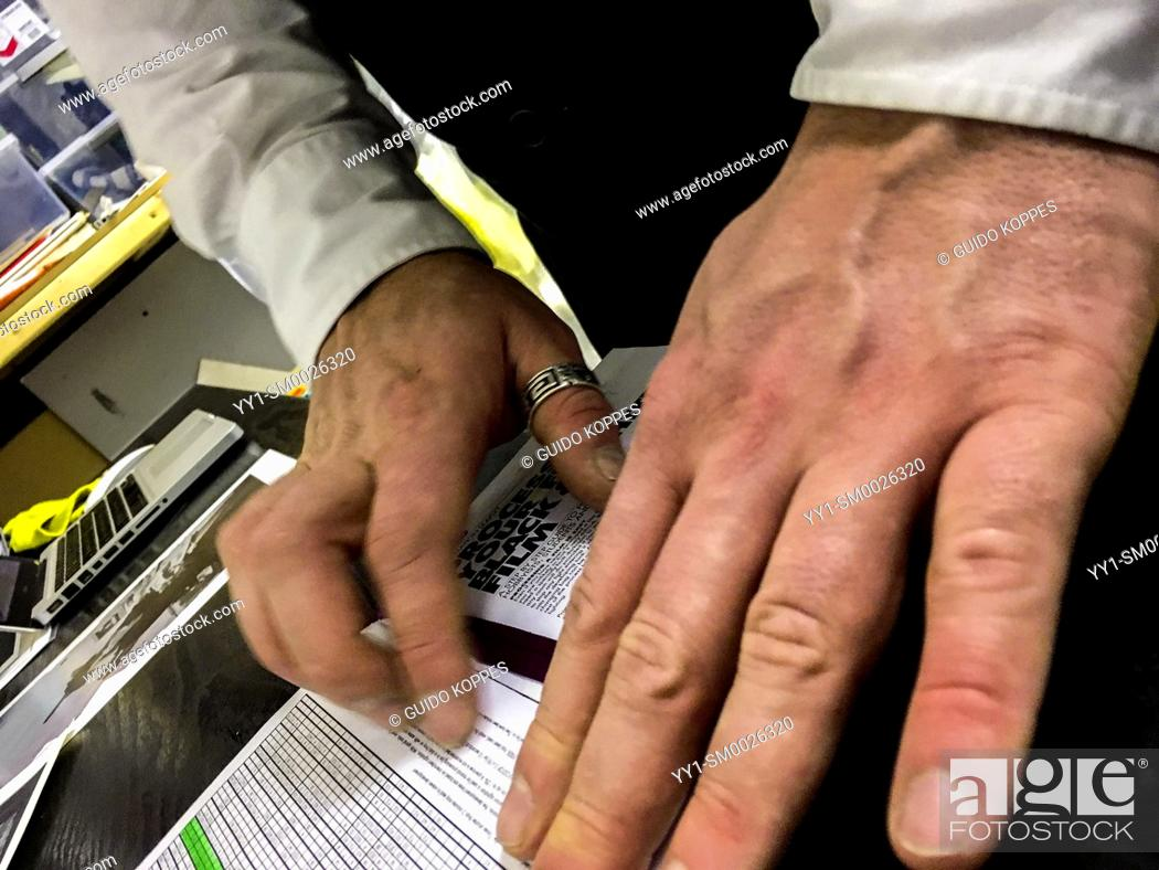 Imagen: Tilburg, Netherlands. Hands en Fingers of a young adult caucasian male searching sheets with chemical info for the right numbers.