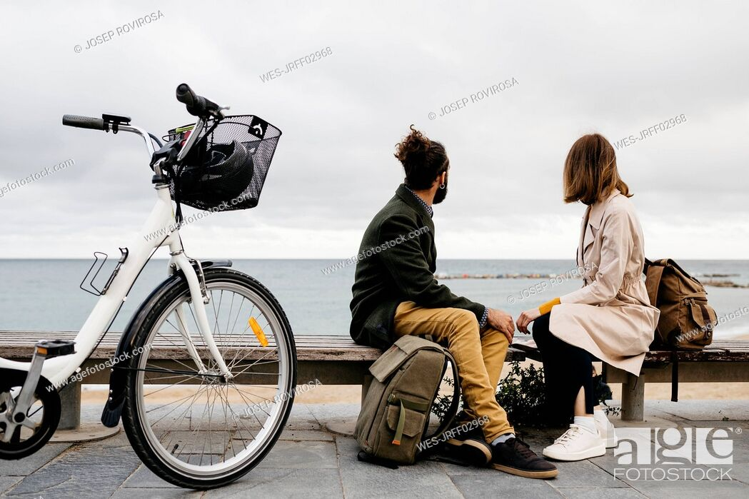 Stock Photo: Couple sitting on a bench at beach promenade next to e-bike looking at the sea.