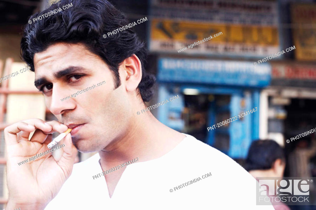Stock Photo: Portrait of a young man smoking a cigarette.