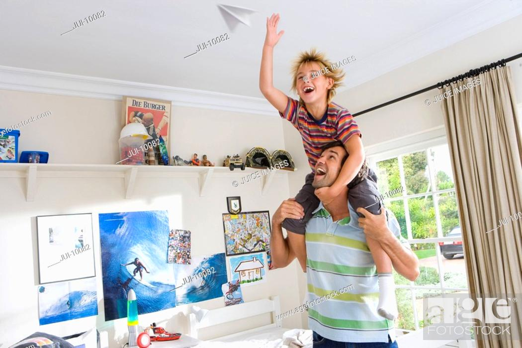 Stock Photo: Boy 6-8 on father's shoulder's, playing with paper dart, smiling.