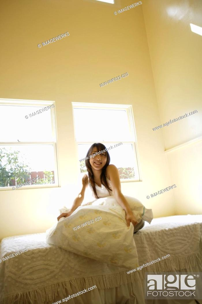 Stock Photo: View of a cheerful woman sitting on bed.