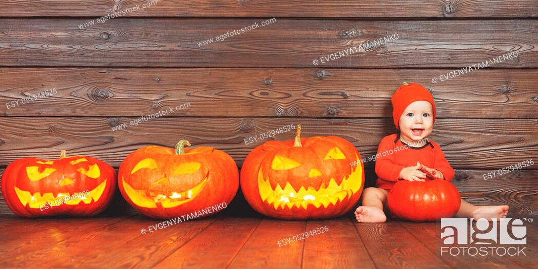 Stock Photo: happy baby in costume for Halloween with pumpkins with burning eyes on wooden background.