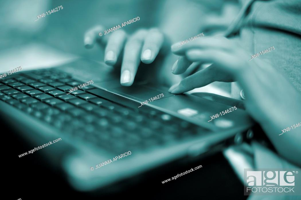 Stock Photo: Hands of a young woman on a laptop.