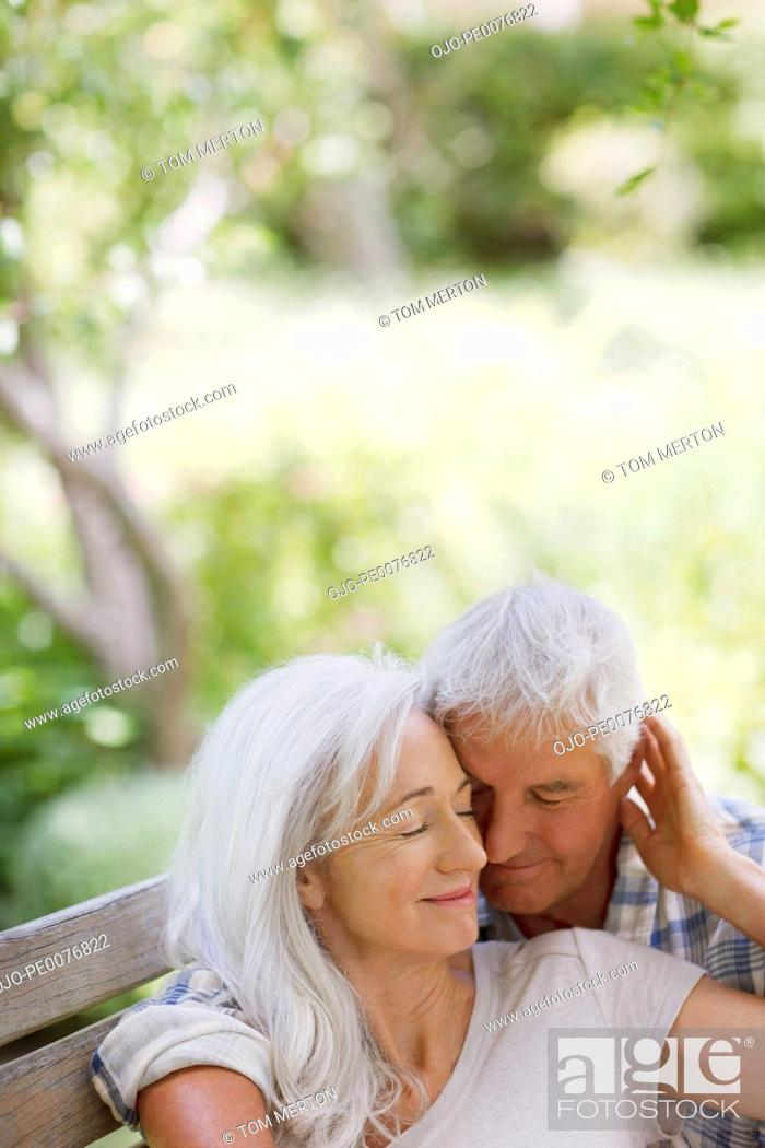 Stock Photo: Senior couple hugging on bench.