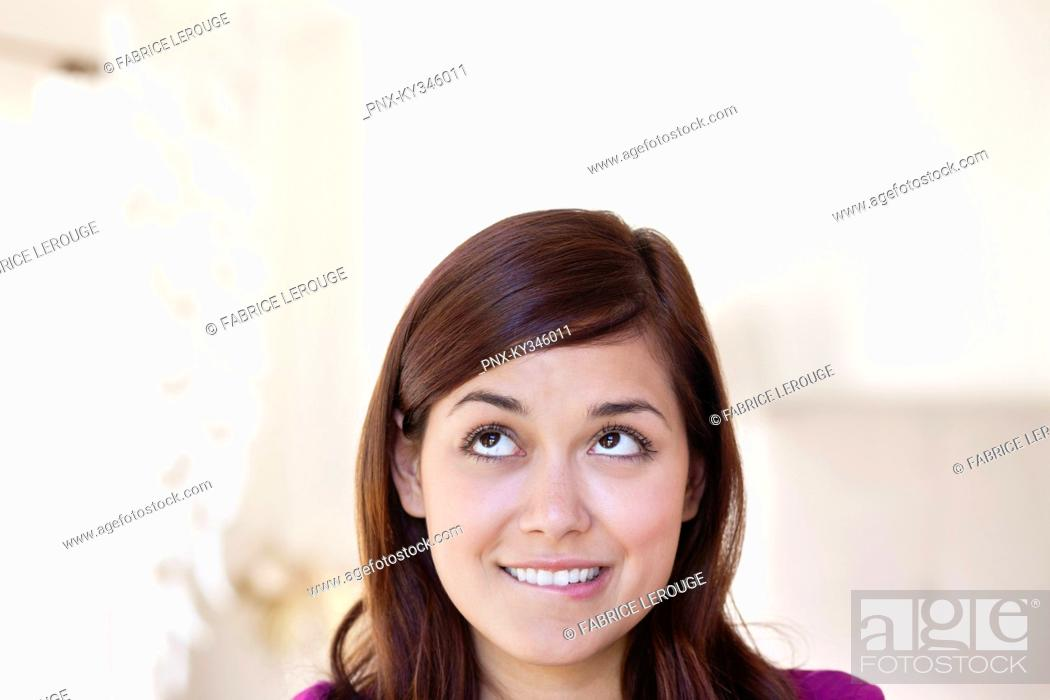 Stock Photo: Young woman looking away while biting lips.