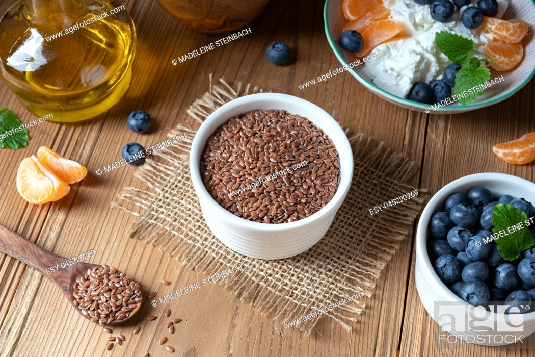 Stock Photo: Flax seeds in a bowl, with cottage cheese, oil and fresh blueberries in the background.