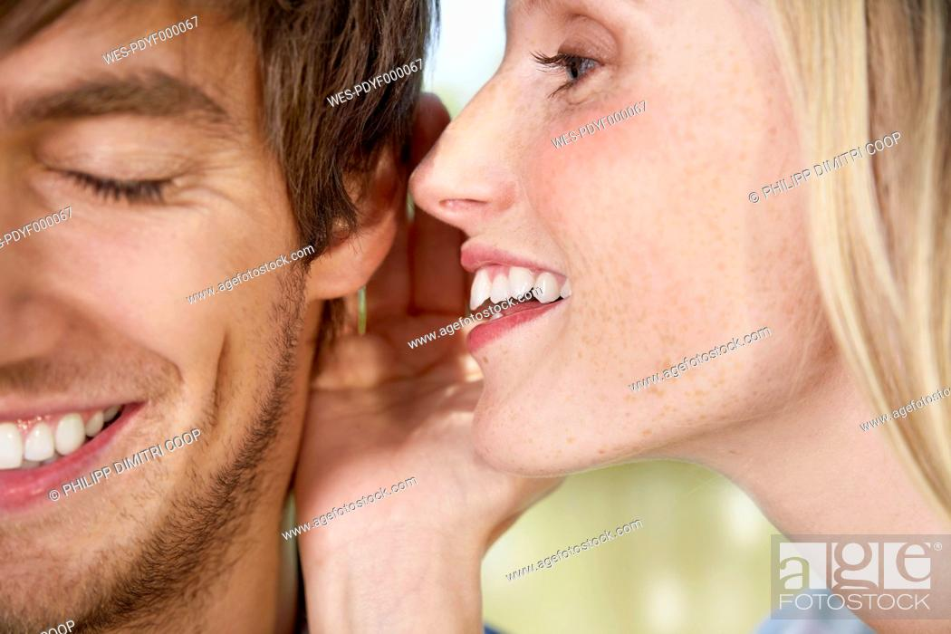 Stock Photo: Germany, Cologne, Young woman whispering to man, close up.