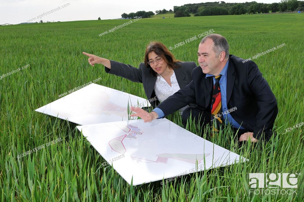 Stock Photo: businesswoman and businessman with blueprints in the field.