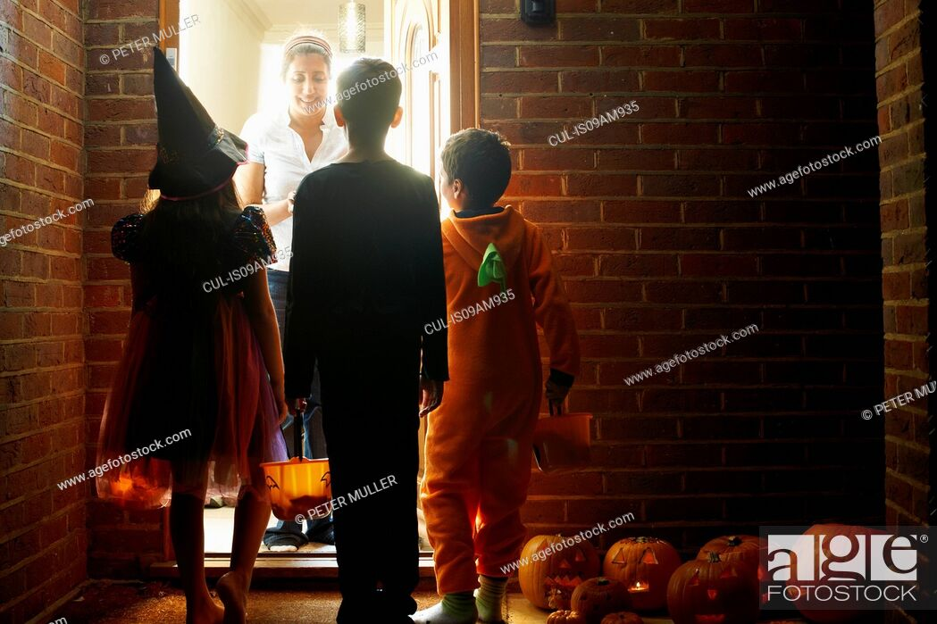Imagen: Rear view of three children wearing halloween costumes trick or treating.