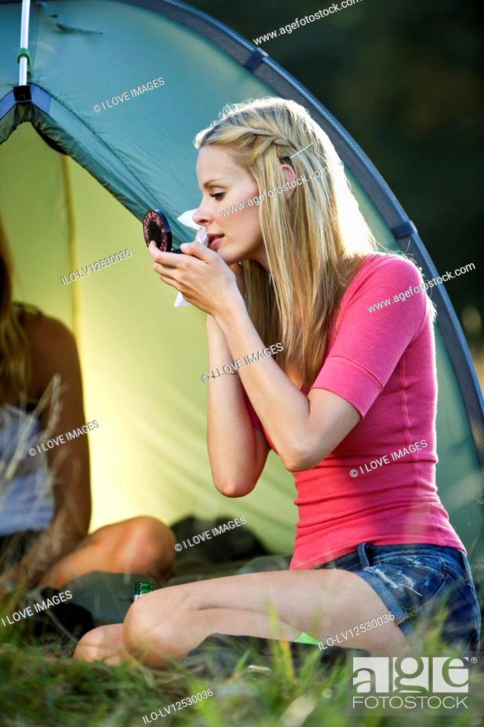 Stock Photo: Two young women camping, one wiping her face.