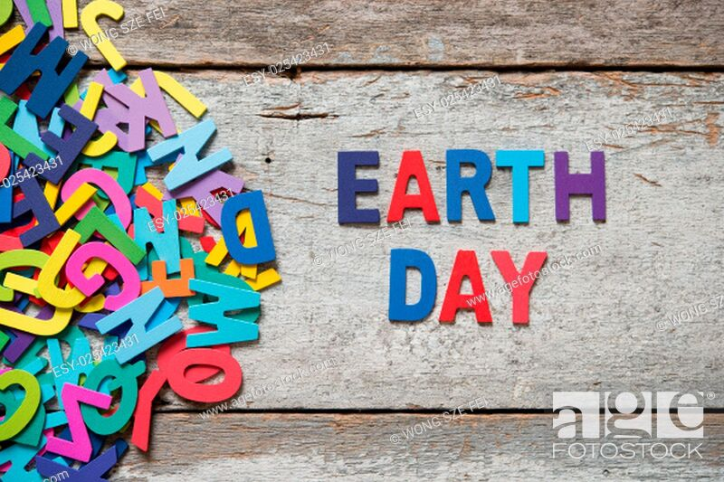 """Stock Photo: The colorful words """"""""EARTH DAY"""""""" made with wooden letters next to a pile of other letters over old wooden board."""