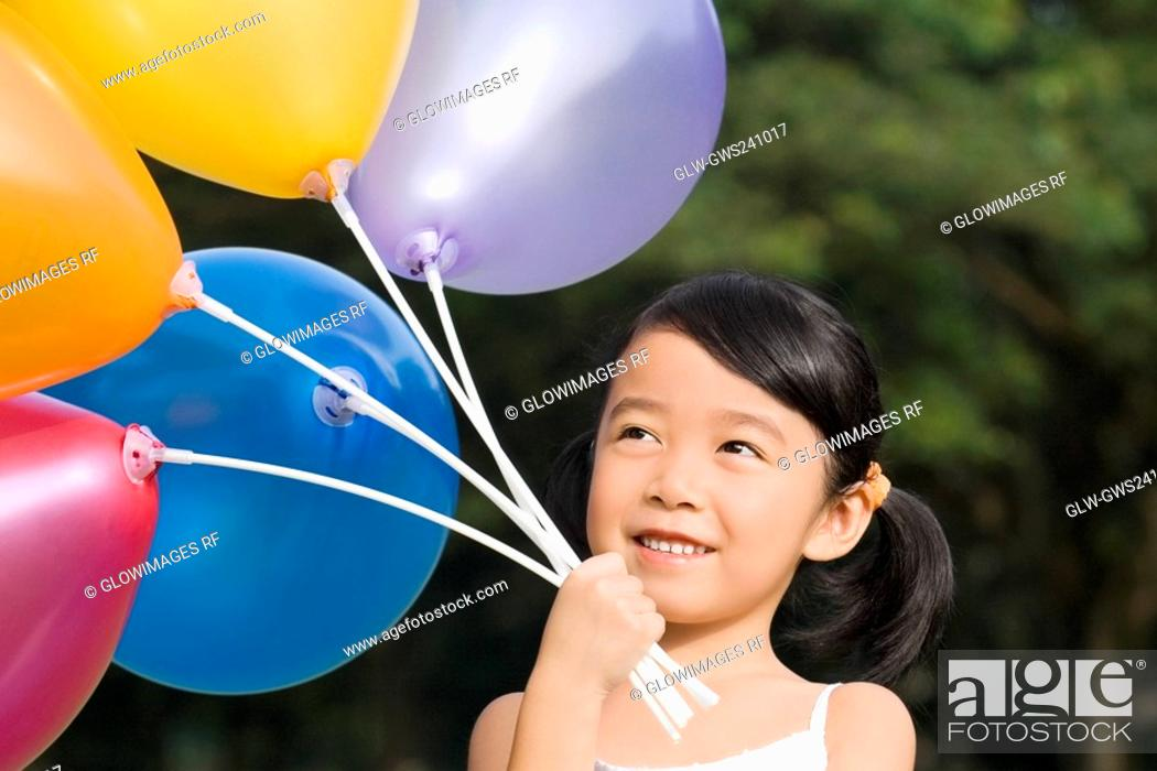 Stock Photo: Close-up of a girl holding balloons.