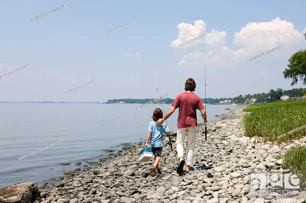 Stock Photo: Father and son walking along beach with fishing rods.