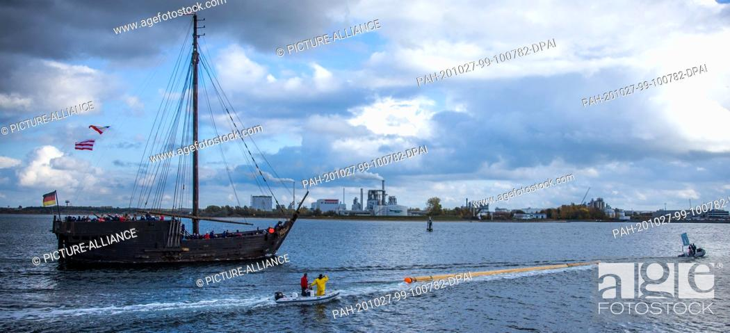 """Stock Photo: 27 October 2020, Mecklenburg-Western Pomerania, Wismar: Accompanied by the cog """"""""Wissemara"""""""" from Poel, the new mast for the sailing ship replica is towed into."""