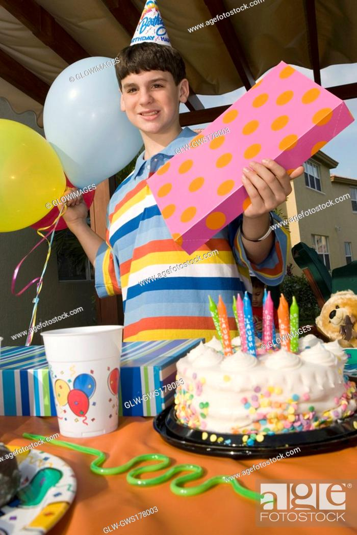 Stock Photo: Portrait of a boy holding a birthday present and balloons.