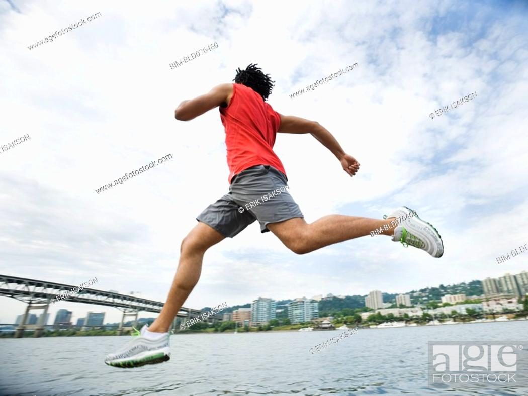 Stock Photo: Mixed race man leaping next to river.