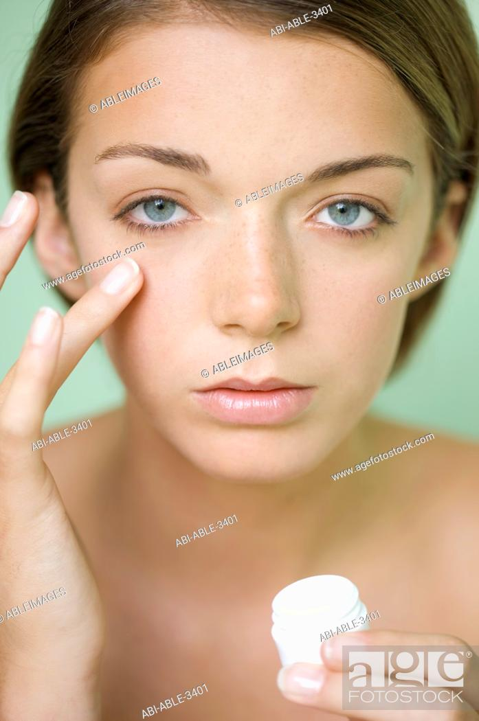 Stock Photo: Young woman applying moisturizer under her eye holding a cream jar.