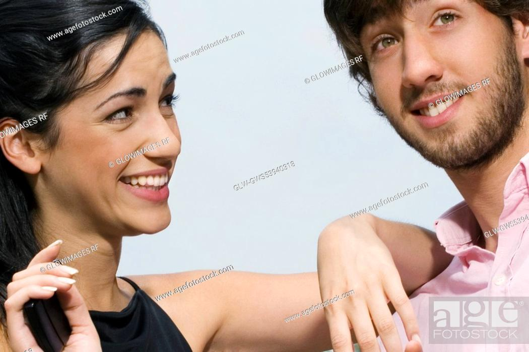 Stock Photo: Close-up of a young woman looking at a young man and smiling.