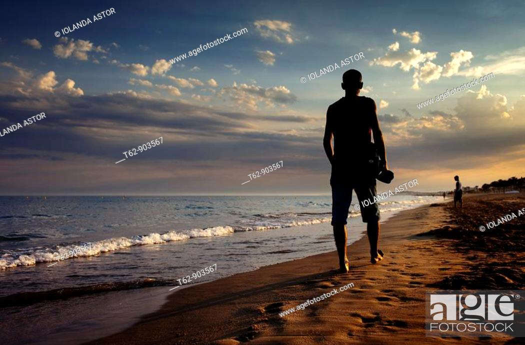 Stock Photo: Young man walking by the seaside in summer at dusk.