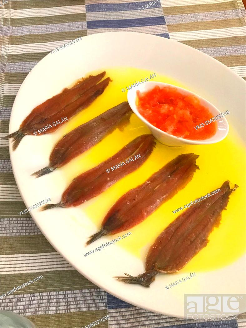Stock Photo: Anchovy fillets with olive oil and tomato.