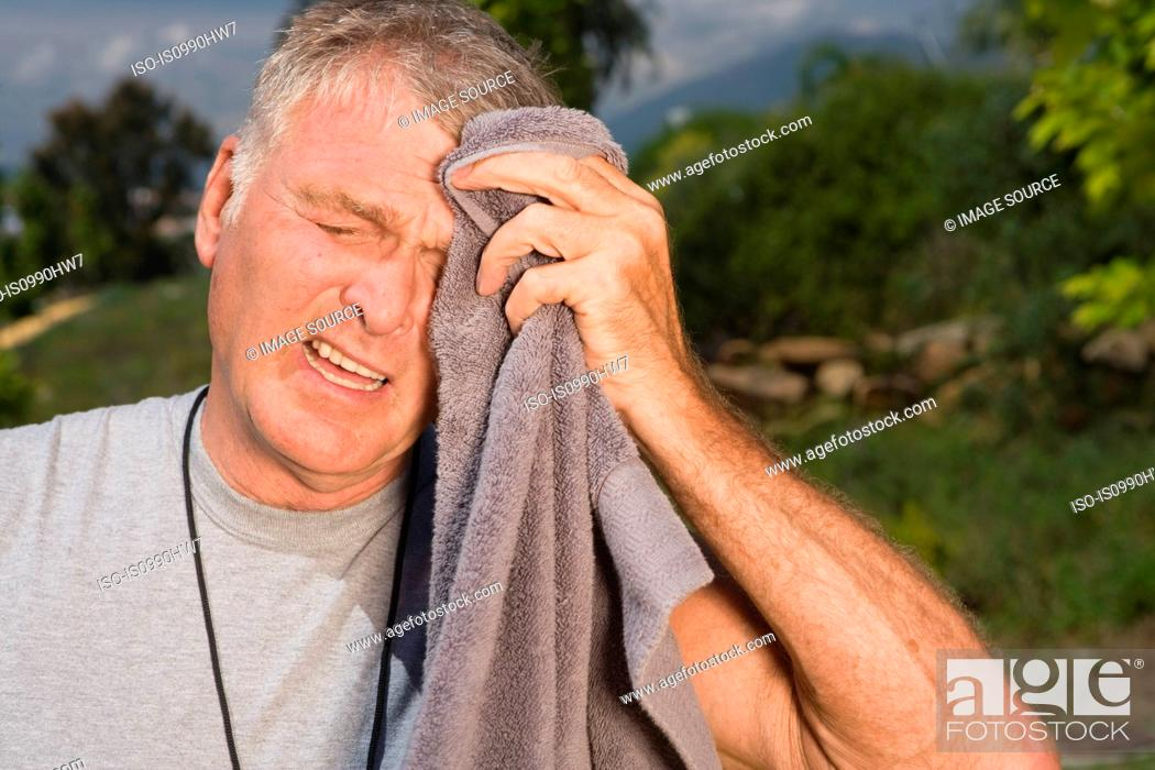 Stock Photo: Senior man wiping face with towel after workout.
