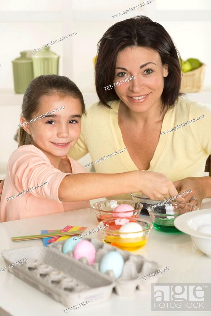 Stock Photo: Mother and daughter coloring Easter eggs.