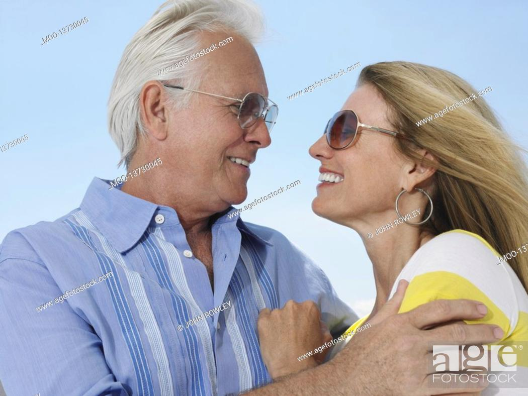 Stock Photo: Middle-aged couple embracing and looking in eyes against sky.