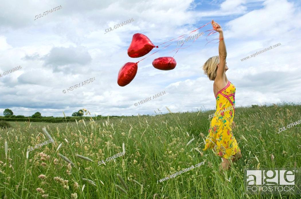 Stock Photo: Woman walking with balloons in field.
