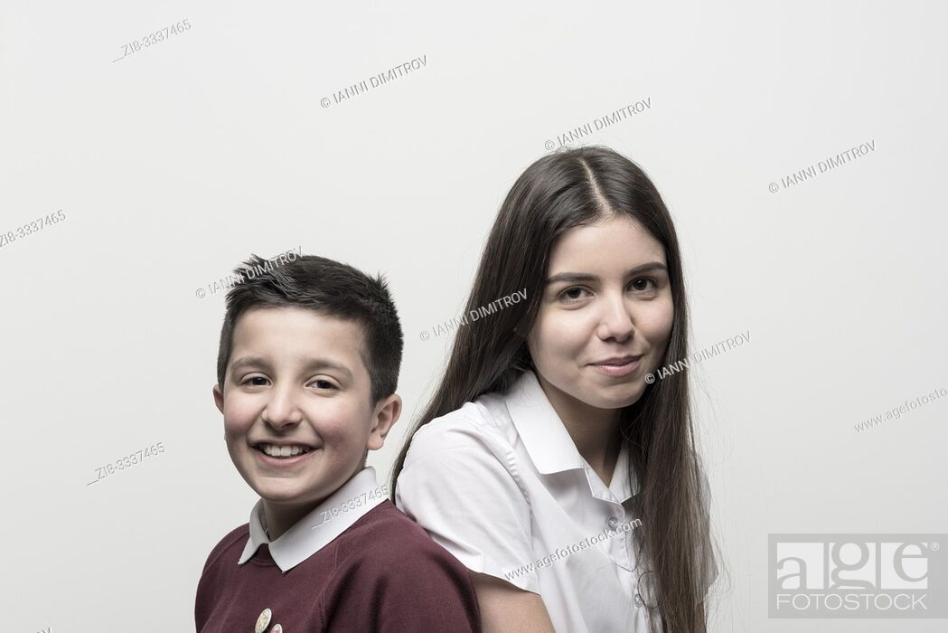 Stock Photo: UK, England, Portrait of 10 years old boy and his teenage sister , both in school unoforms . Studio settings.