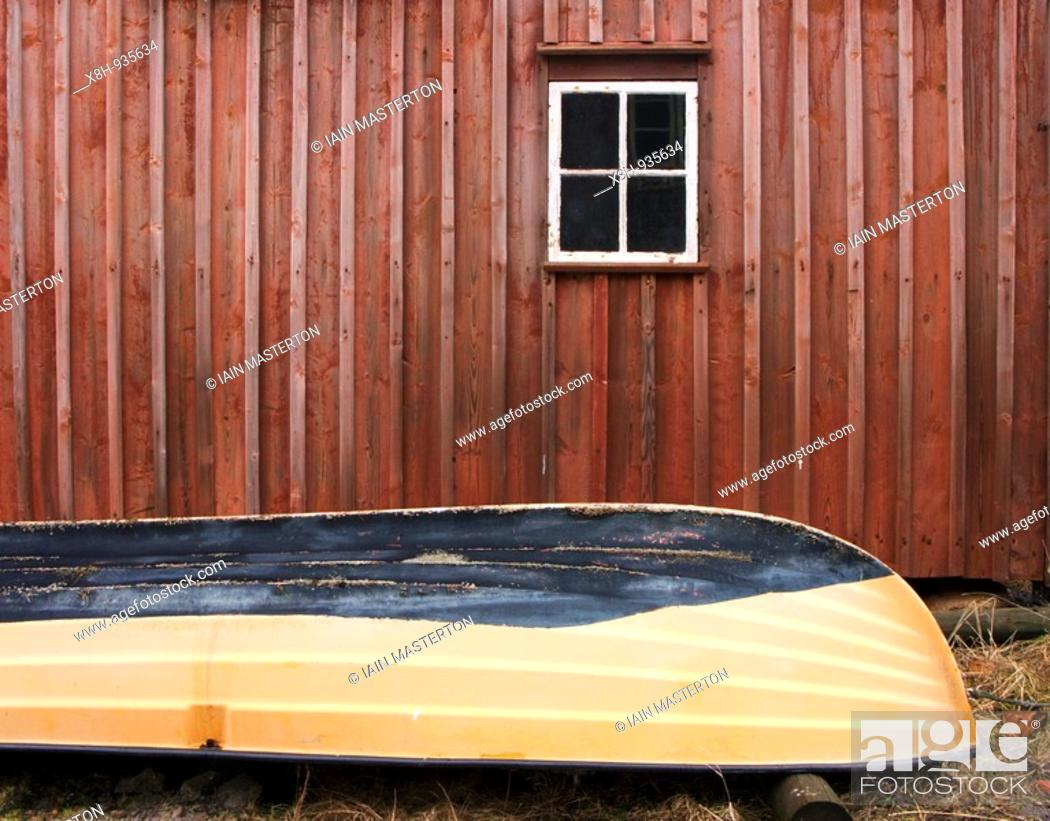 Stock Photo: Detail of rowing boat beside traditional red timber boathouse in village of Mollosund on Bohuslan Coast of Sweden.