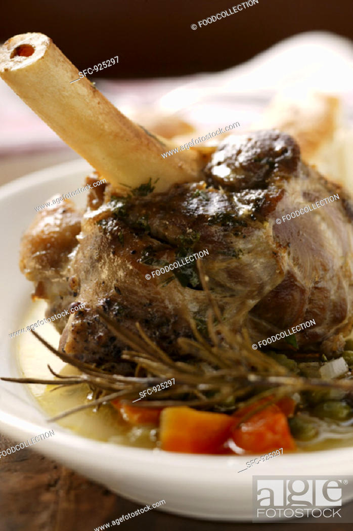 Stock Photo: Braised lamb shank with vegetables & rosemary on plate.