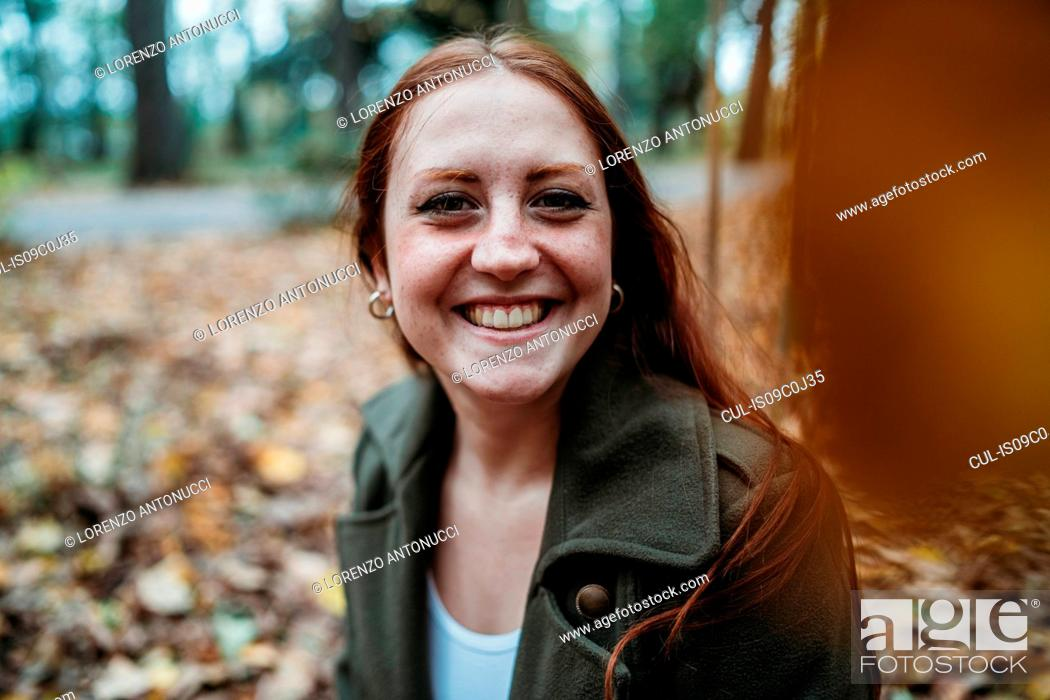 Stock Photo: Young woman with long red hair in autumn park, portrait.