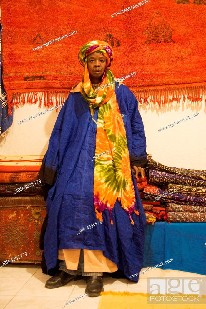 Stock Photo: Colourful outfit of an employee in a carpet shop in Tafraoute, Ameln valley, Anti-Atlas mountains, Morocco.