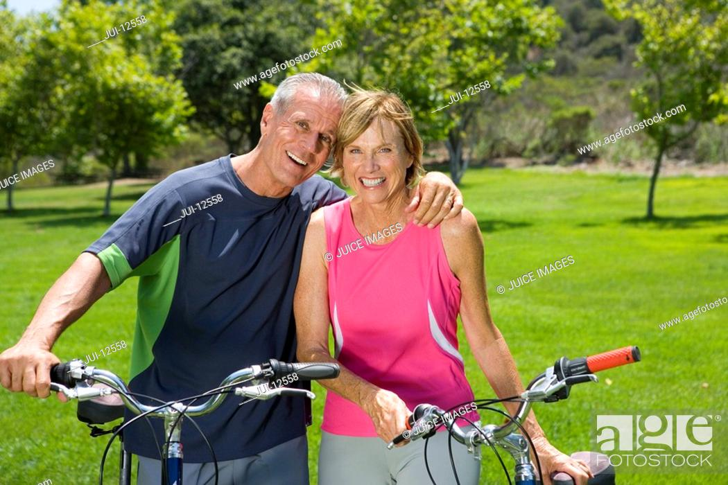 Stock Photo: Mature couple with bicycles outdoors, man with arm around woman, smiling, portrait.