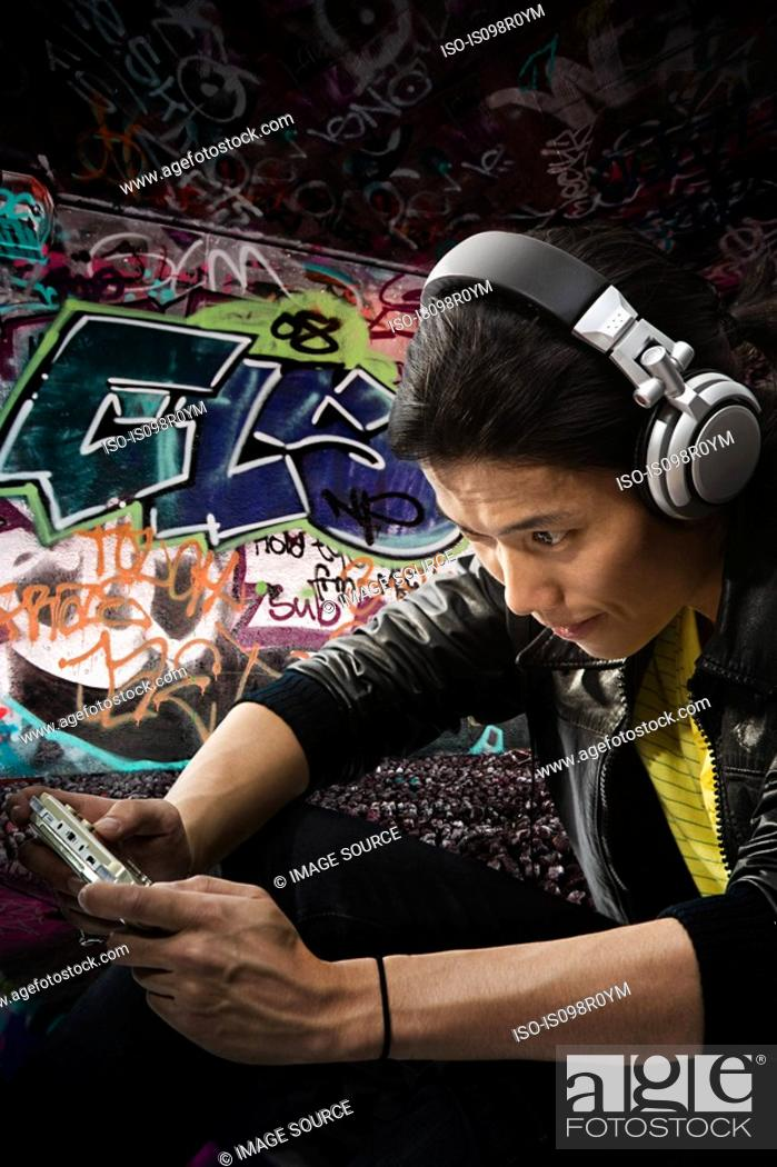 Stock Photo: A young man playing on a handheld computer.